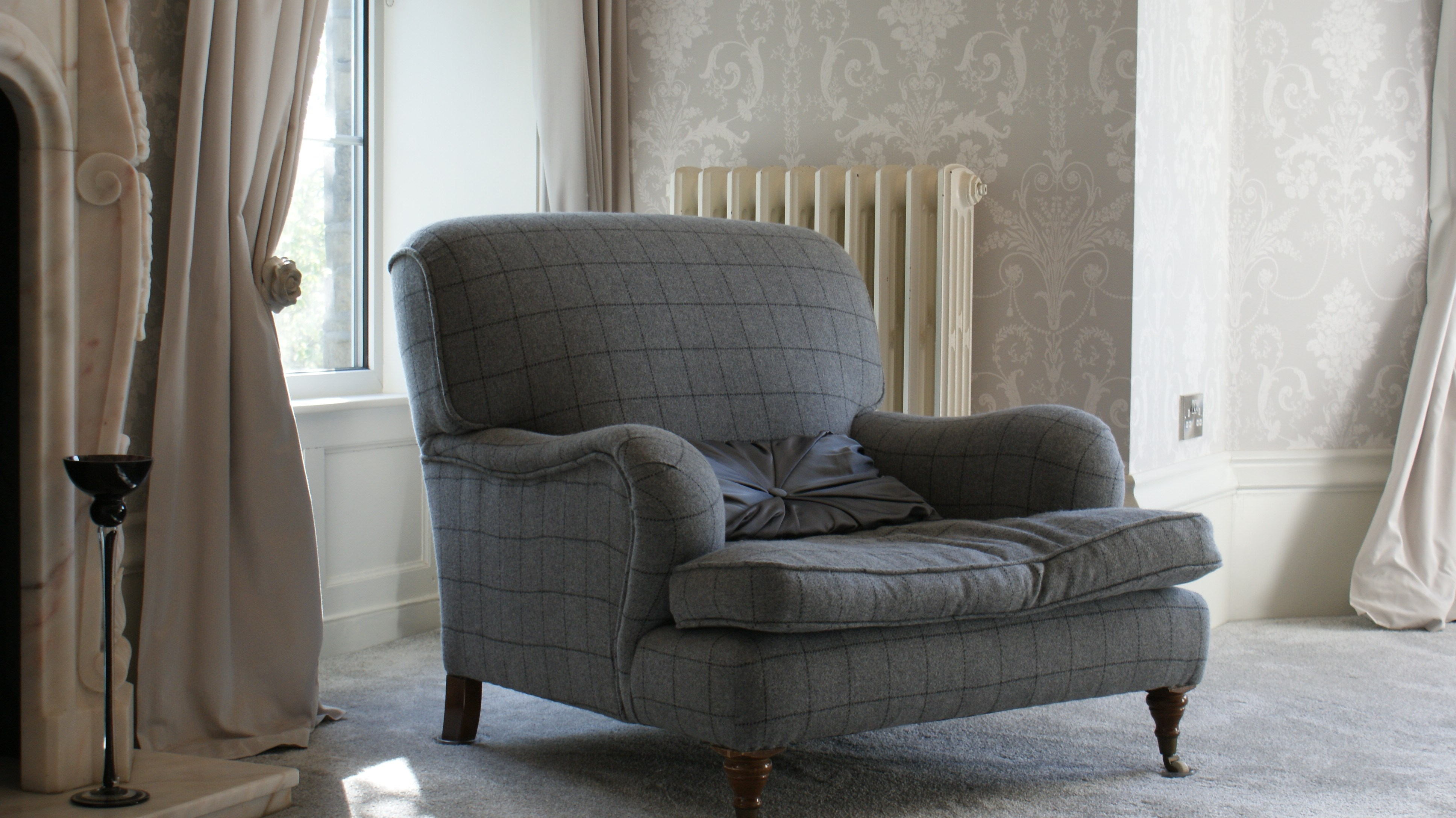 Armchair in grey fabric against backdrop of curtains