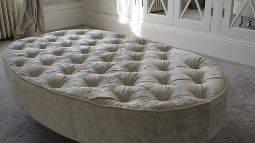 Very large footstool with buttoning and deep foam finish.
